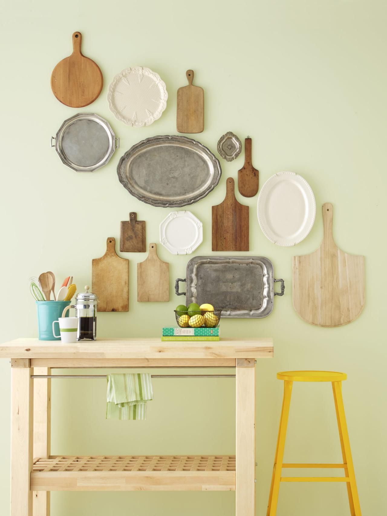 Show off serving pieces on a kitchen wall. Hang wood cutting boards ...