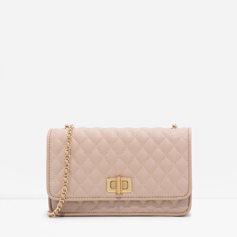 Nude quilted small sling bag featuring a weave chain strap. Fastens with a turn-lock closure.