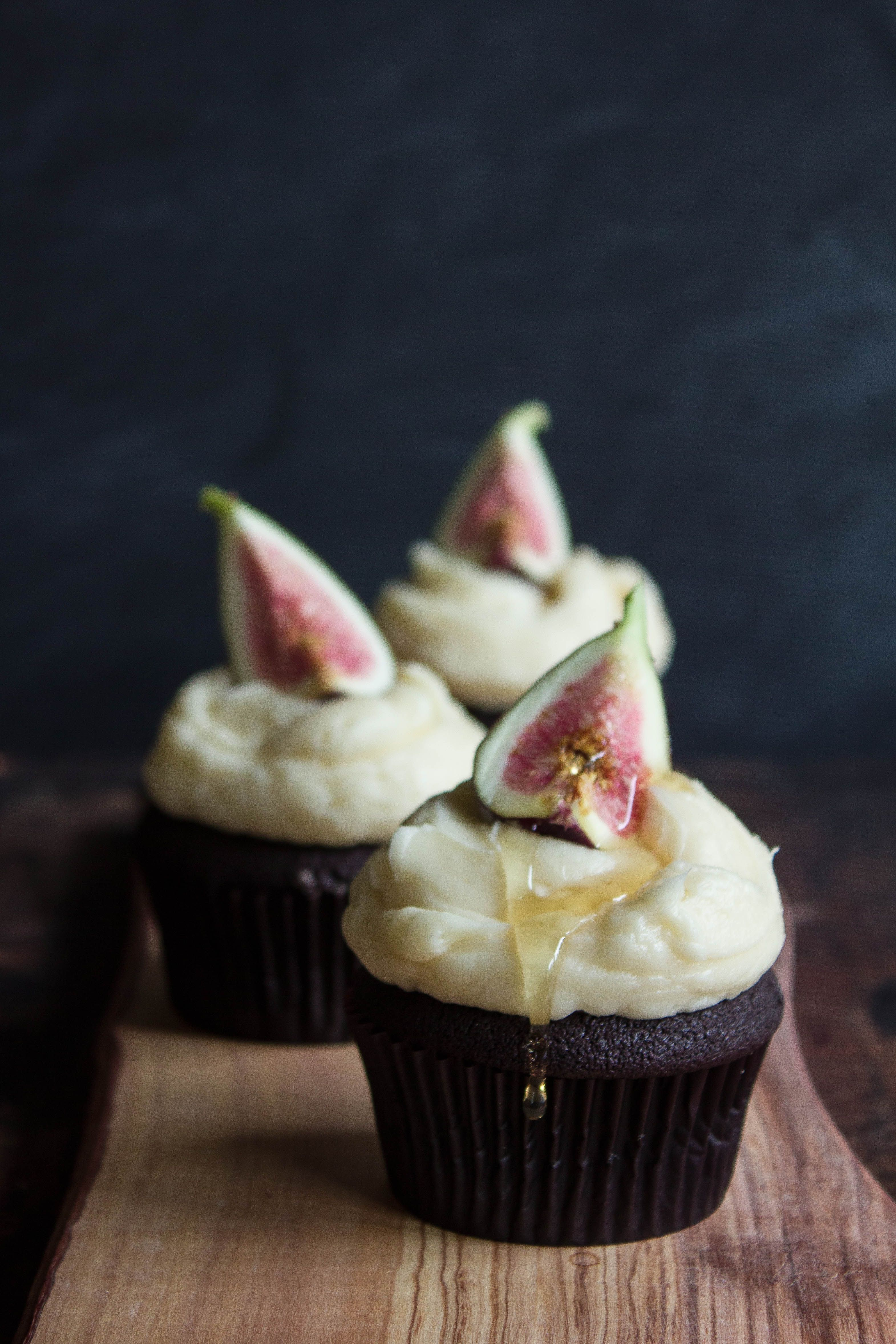 Chocolate cupcakes topped with fresh figs and drizzled with honey