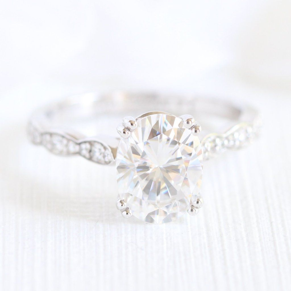 Oval solitaire engagement ring features a forever one moissanite set