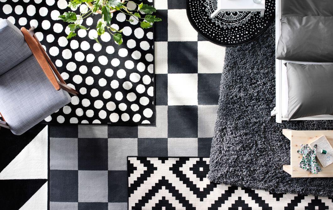 Vrstvy čierno-bielych kobercov s rôznou štruktúrou a vzormi na zemi v obývacej izbe.