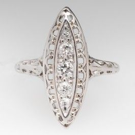 This lovely 1940's navette ring features a mix of old Euro and brilliant cut round diamonds along with beautiful details. The ring sits low on the finger and has an elegant understated look. It is comfortable to wear and is in great shape for it's age. It is crafted of platinum. We offer complimentary resizing prior to shipping.