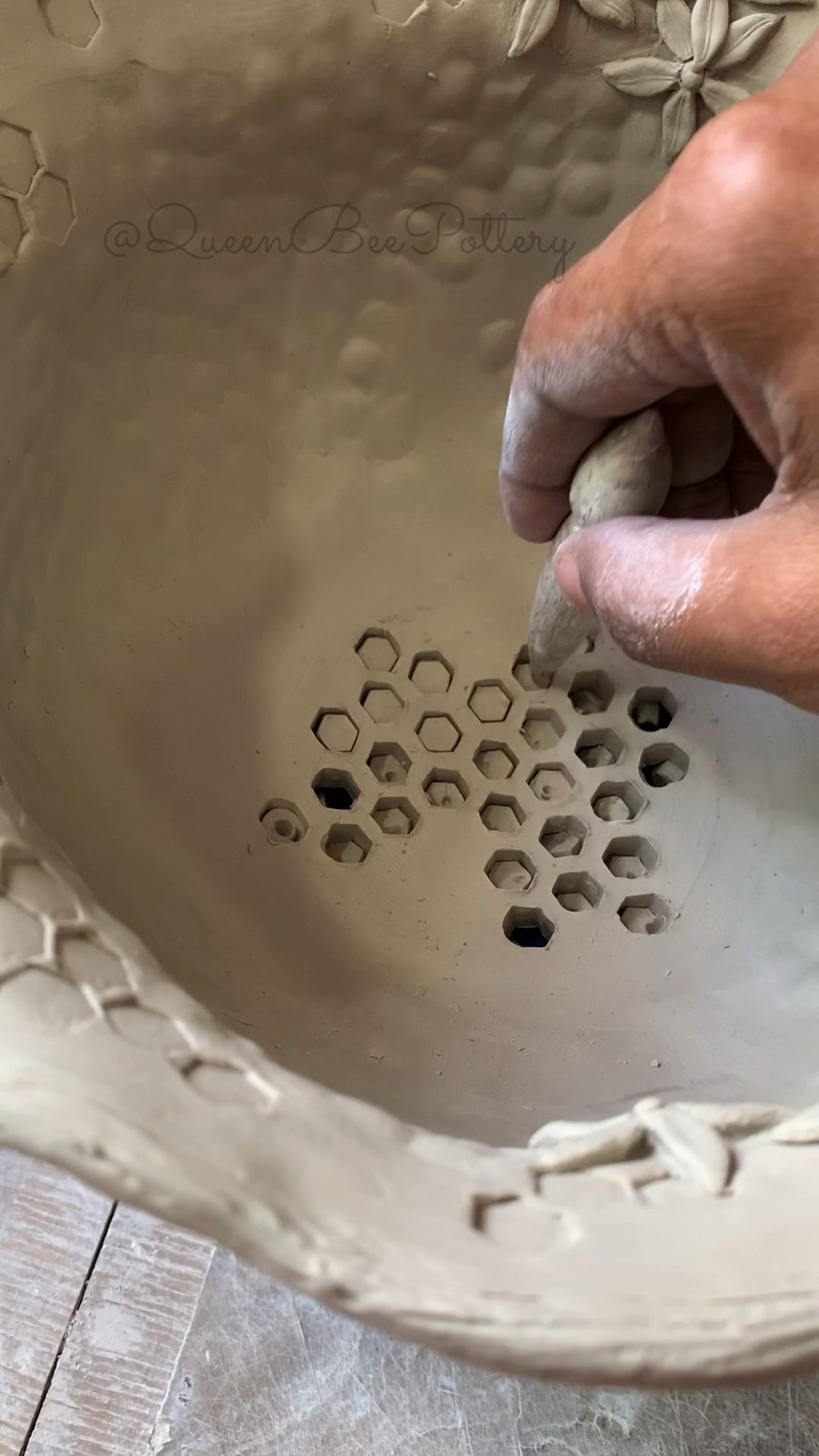 Porcelain bee inspired pottery colander being created.