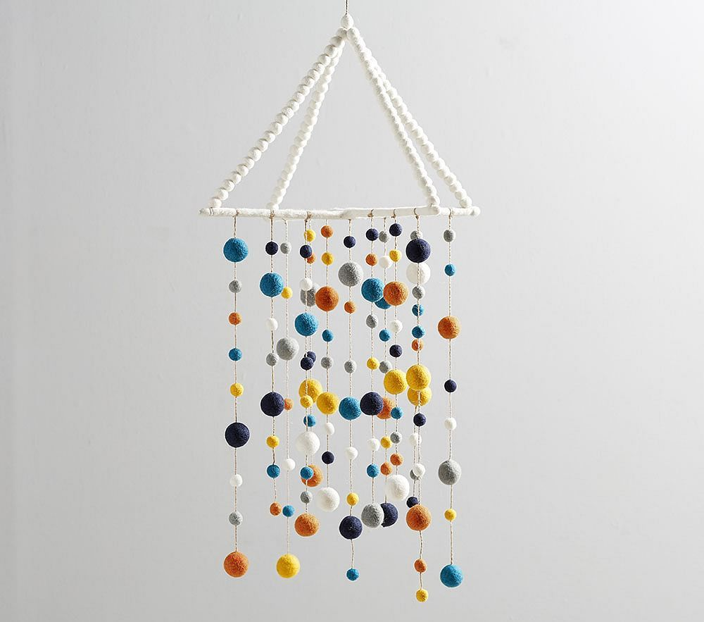 Designed in collaboration with west elm, this Pom-Pom Mobile engages your baby's budding fascination with shape and color. It's hand-felted in Nepal from 100% wool in a Fair Trade Certified(TM) facility, directly benefiting the artisans who craft it. DETAILS THAT MATTER Made of wool and jute. Hangs from ceiling with loop. Mobiles should be placed well out of arm's reach of your baby. Once your baby is able to sit up, mobiles should be removed. KEY PRODUCT POINTS Spot clean. Imported.