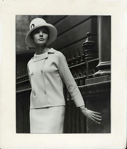 1968 Photograph of a female model wearing a light coloured woolen, hip length, double breasted jacket, with a matching pencil skirt. The garments in the photograph were designed by Richard Charlupski and made by Edda Azzola of Ricardo Knitwear, Melbourne.