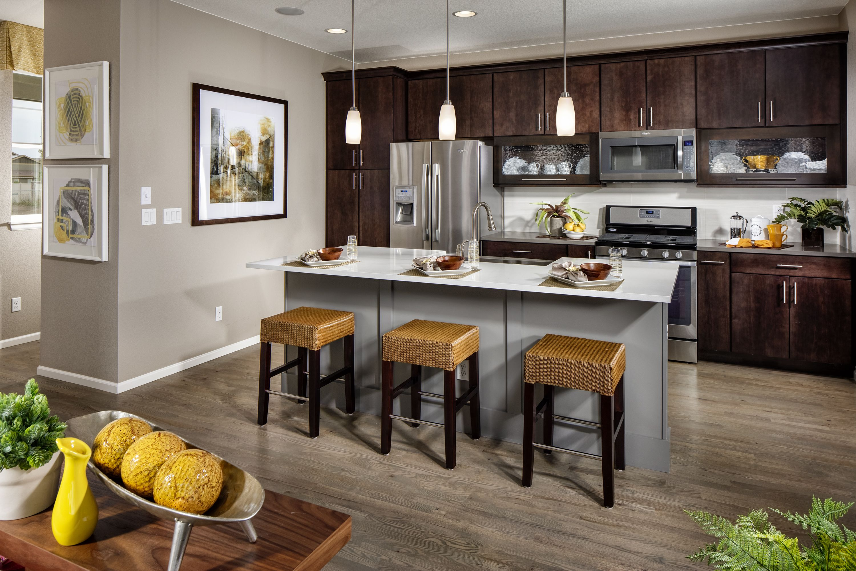 Kitchen featuring a white island with dark brown cabinets ...