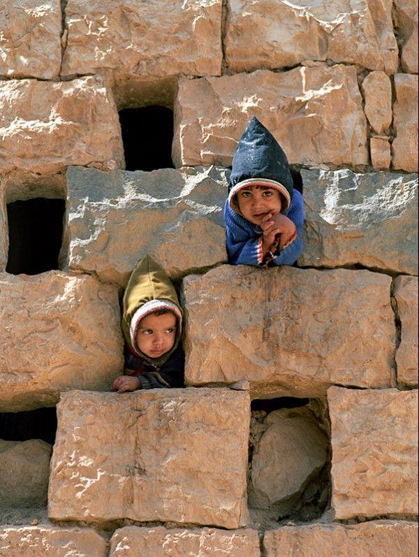 Children of Yemen play within natures stones. Unlike Americans, children have no playground equipment so they use the world around them.