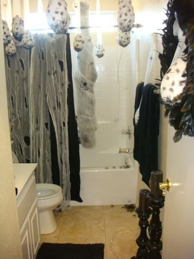 quick and easy way to decorate the bathroom effectively. some creepy cloth, bags of fake spiders, and cheezy spider webbing.