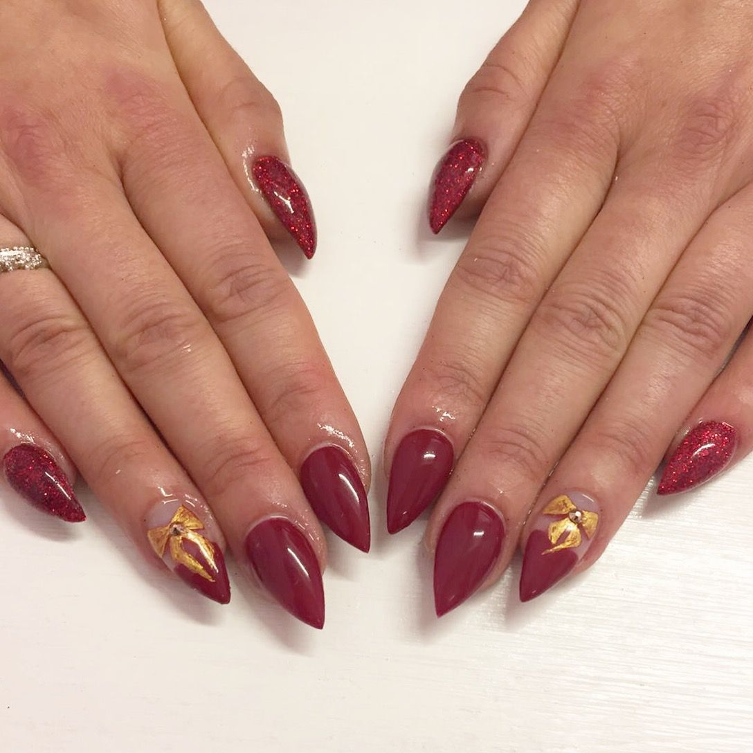 Dark red stiletto nails with Christmas bow freehand nail art. | Our ...