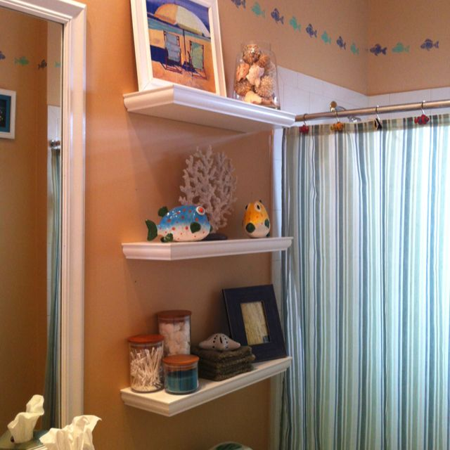 Floating shelves in a beach fish themed bathroom home for Fish themed bathroom