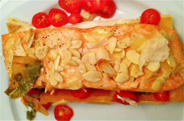 Almond Crusted Salmon baked over puff pastry with pesto and cherry tomatoes.