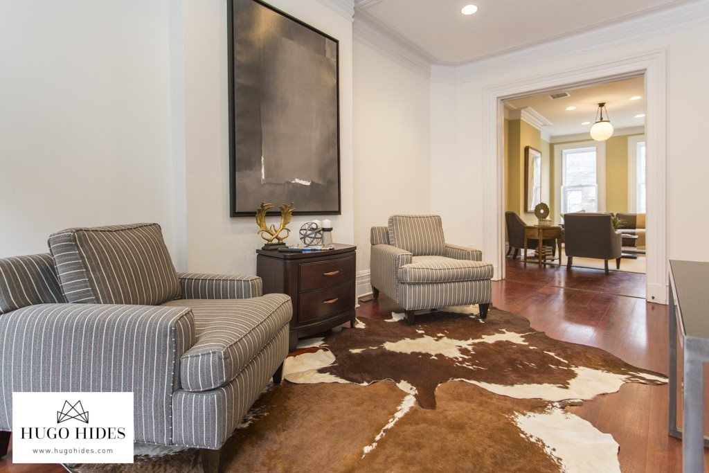 Layering Rugs Is A Fun Way To Decorate A Large Space Two Complementary Cowhides Or A Cowhide With A Traditional Rug Both L Cow Hide Rug Zebra Rug Layered Rugs