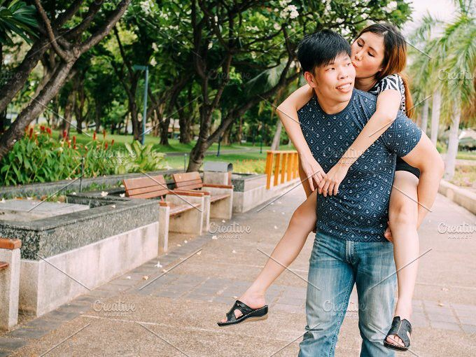 Asian boyfriend carrying his smiling girlfriend in public park. People Photos. $8.00