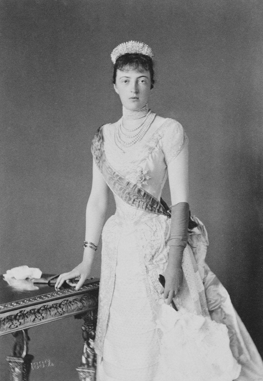 Anastasia Mikhailovna, Grã-duquesa da Rússia, em 1889, em pé e usando um vestido de Estado com a Ordem Star e Sash. Ela descansa a mão direita sobre uma mesa.