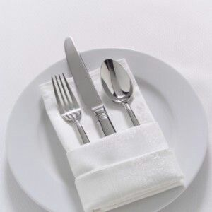 white plates with white polyester napkin rectangle pocket fold and silver ware