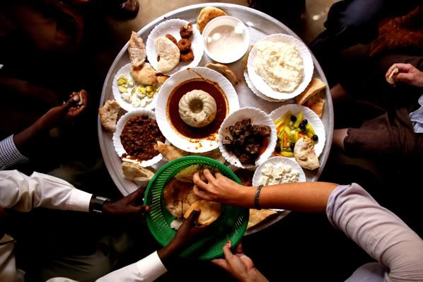 traditional sudanese grub. clockwise from top: yoghurt, rice, pickled things, meat, cheese, bread, beans, eggs, falafel and (at center) asida (stew with flour paste).