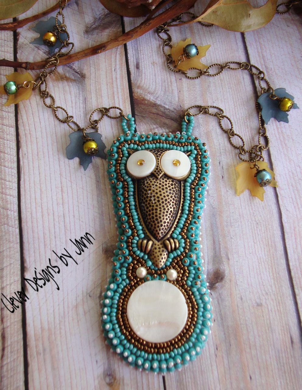 Owl Beaded Necklace .. A cute brass owl with eyes of mother of pearl and a large mother of pearl cab are the focal beads for this sweet necklace .. 3 different sizes of seed beads, beads & pearls, lucite leaves, chain, and flat back crystals are also used to create this necklace .. FOR SALE .. $75.00