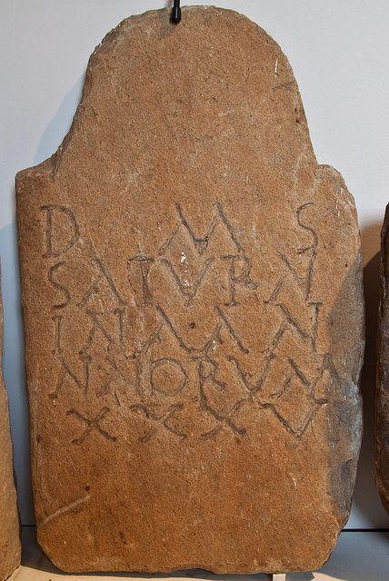 Estela de Saturnina    D(is) M(anibus) S(acrum)/ SATVRN/INA  AN/NNORUM XXXV    Consagrado aos deuses Manes. A Saturnina, de 36 anos.    Procedencia: Boimente, Castriz, Sta. Comba, A Coruña.