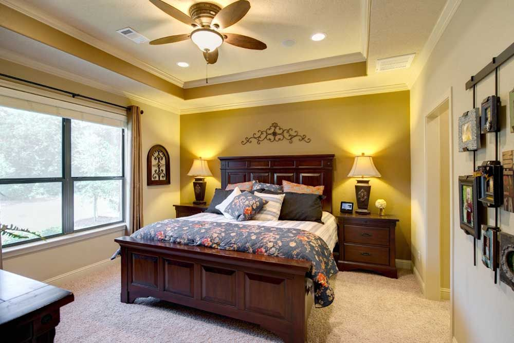The master bedroom features a tray ceiling with crown molding detail and recessed lighting a Master bedroom ceiling lighting ideas