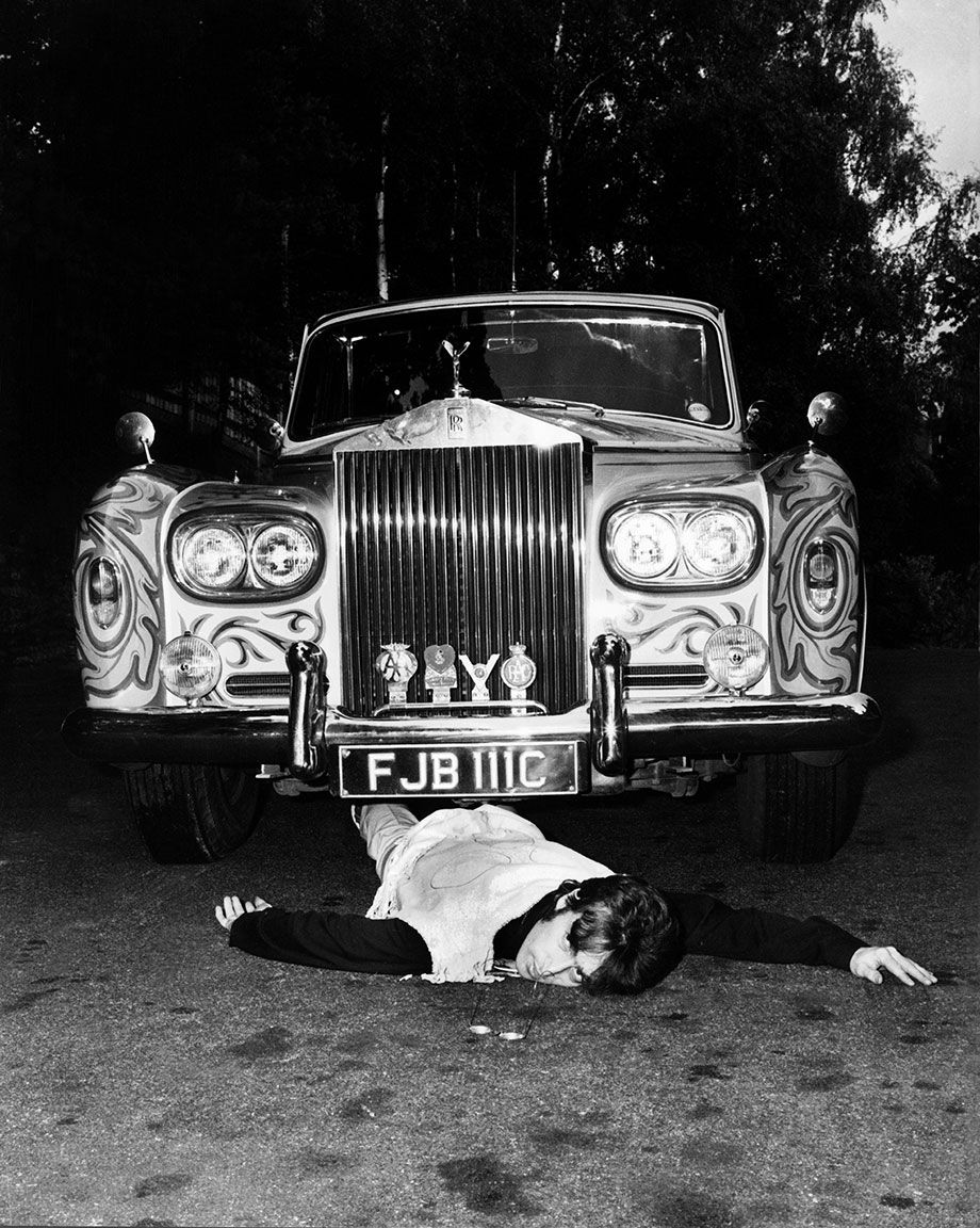 John Lennon acting like he was run over by his own car, a ROLLS ROYCE covered with a psychedelic paint. (Photo by Keystone-France/Gamma-Keystone via Getty Images)