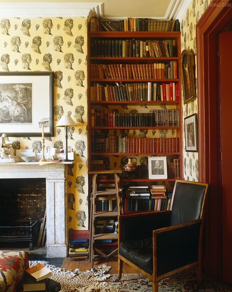 wonderfully eccentric English corner with wallpaper, black leather chair, leather books, animal skin, picture of Shakespeare and ladder