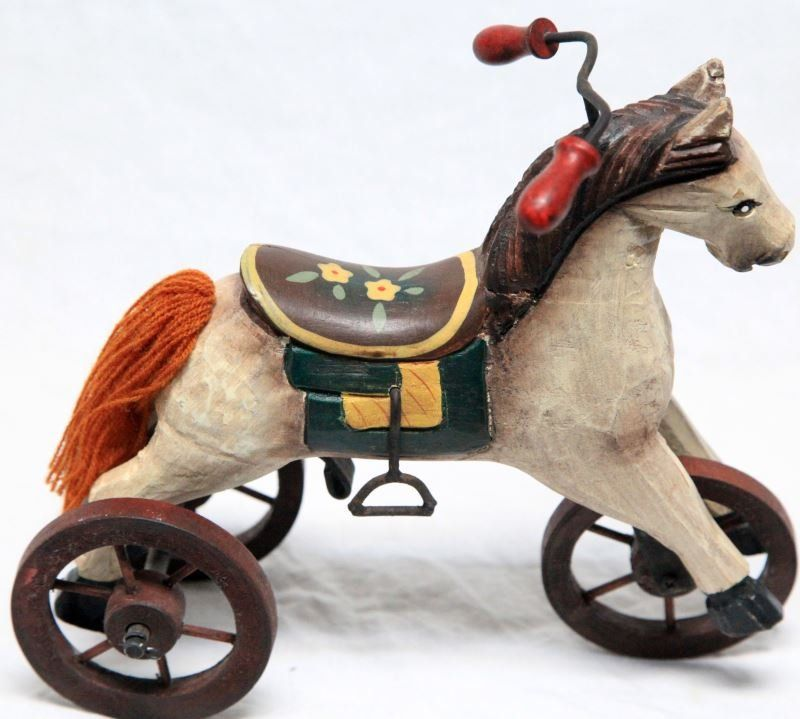 A carved wood horse on a tricycle framed with moving, wooden wheels, metal stirrups and handlebar. Tail is made with yarn