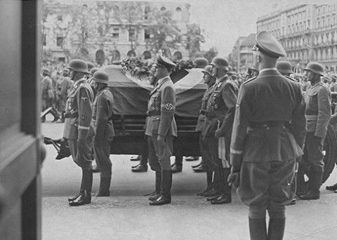 Reichsfuehrer-SS Heinrich Himmler looks on as Reinhard Heydrich's coffin is carried out from the Reich chancellery for burial.