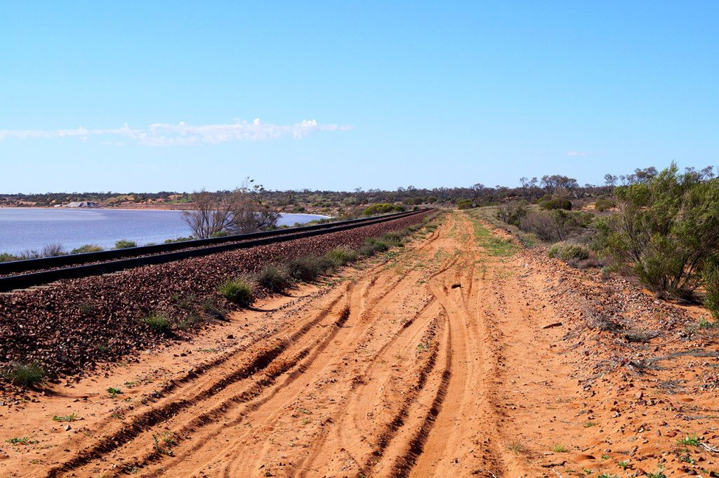 The sandy track which leads up to and over the Ghan railway track near a salt flat in the Australian Outback