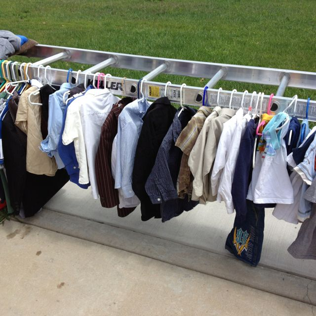 Great idea for displaying clothes at a garage sale! Turn a ladder