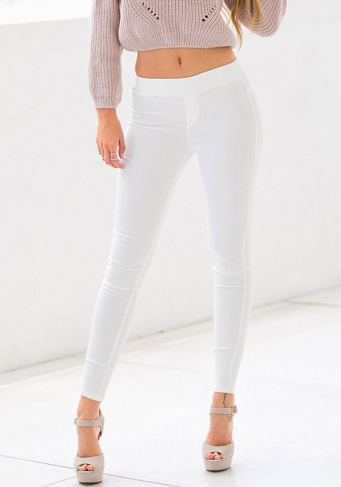 Front shot of model in white skinny high-waisted pants