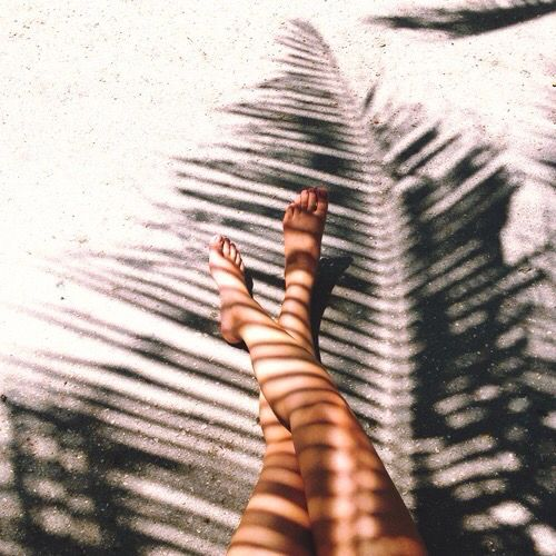 6e6dd2cd3ee Palm leaf frond shadow over beach ocean sea sand in summer barefoot and  bracelets of string like a boho bohemian gypsy hippie