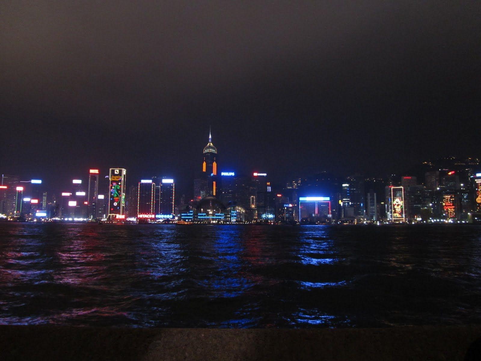una veduta notturna dei grattacieli di Hong Kong illuminati suggestivamente da luci led colorate