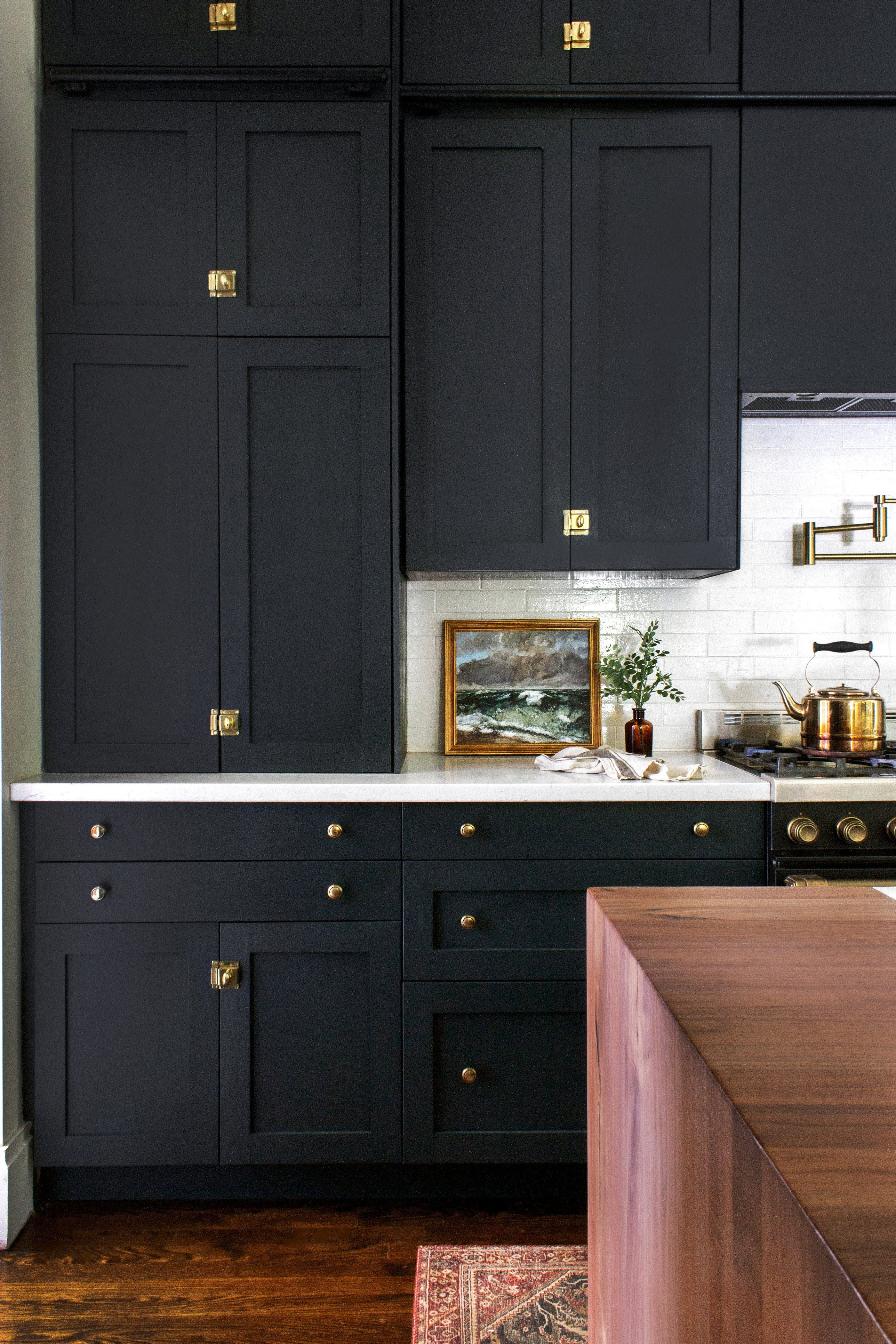 Brass Accents And Ebony Doors Make For A Darkly Dramatic Kitchen