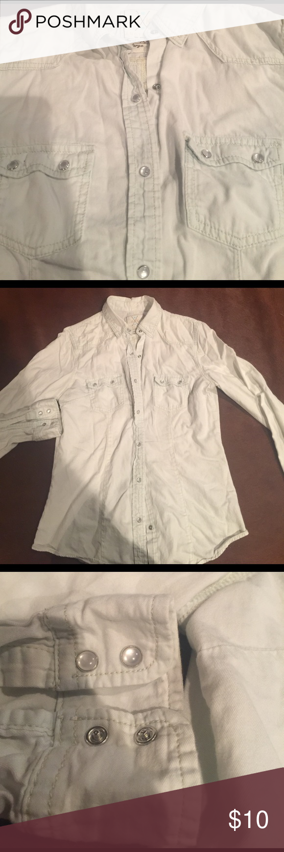 💯 % Cotton Angel Kiss Denim shirt This shirt is so light blue it is almost white.  It is a large but fits a medium. Has a fitted waist and darts in back for a fitted look. It is so soft it's like wearing a t-shirt.  Has awesome pearl like snaps. angel kiss Tops Button Down Shirts