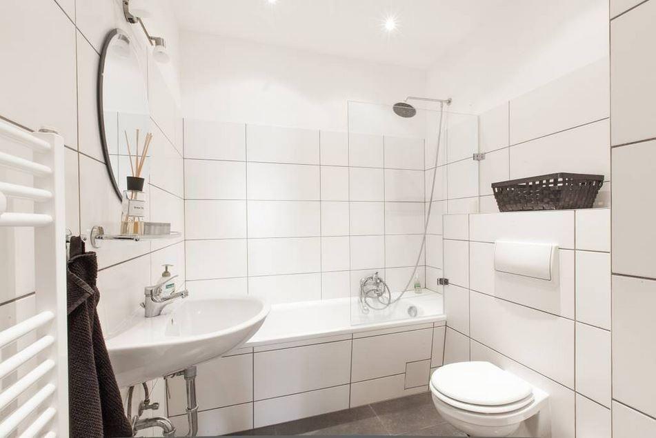 Hell gefliestes Badezimmer mit Badewanne und Handtuchhalter