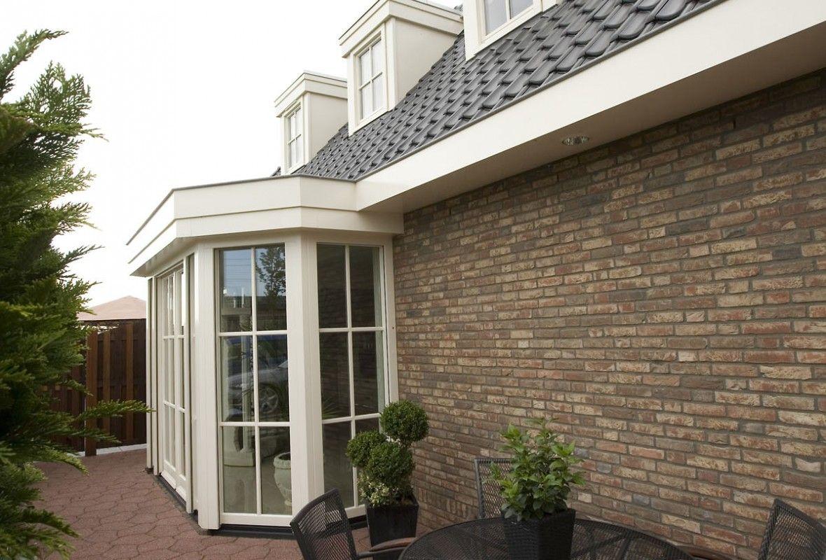 Door een lichte serre die uw woonkamer met de tuin verbindt, kunt u heerlijk van de natuur genieten.