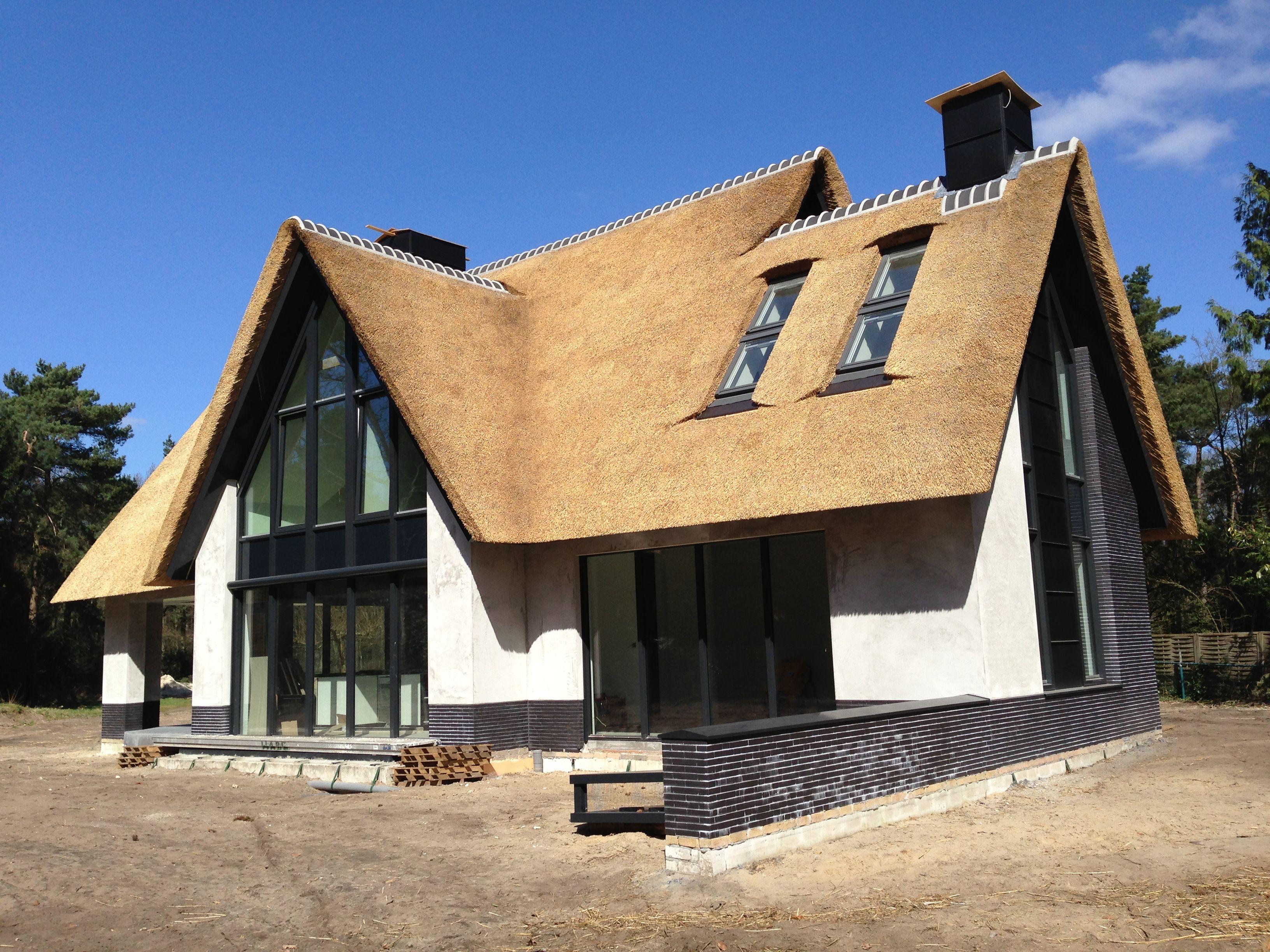 Hoe veel raam er uit ziet bij rieten dak en wit huis ; combinatie