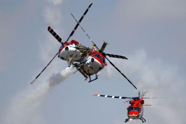 Helicópteros de la Fuerza Aérea india cruzan los caminos en su presentación de acrobacias aéreas en la inauguración de Aero India 2013. (AP)