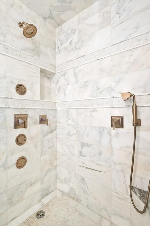 Calcutta Gold Marble Clad Walk In Shower Is Accented With White Tumbled Marble Mosaic Border Tiles Gold Tiles Bathroom Calcutta Gold Marble Marble Shower Tile
