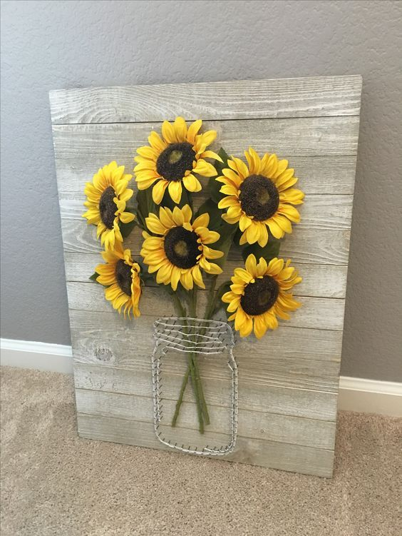A Rustic Pallet Sign With Wire And Faux Sunflowers Is
