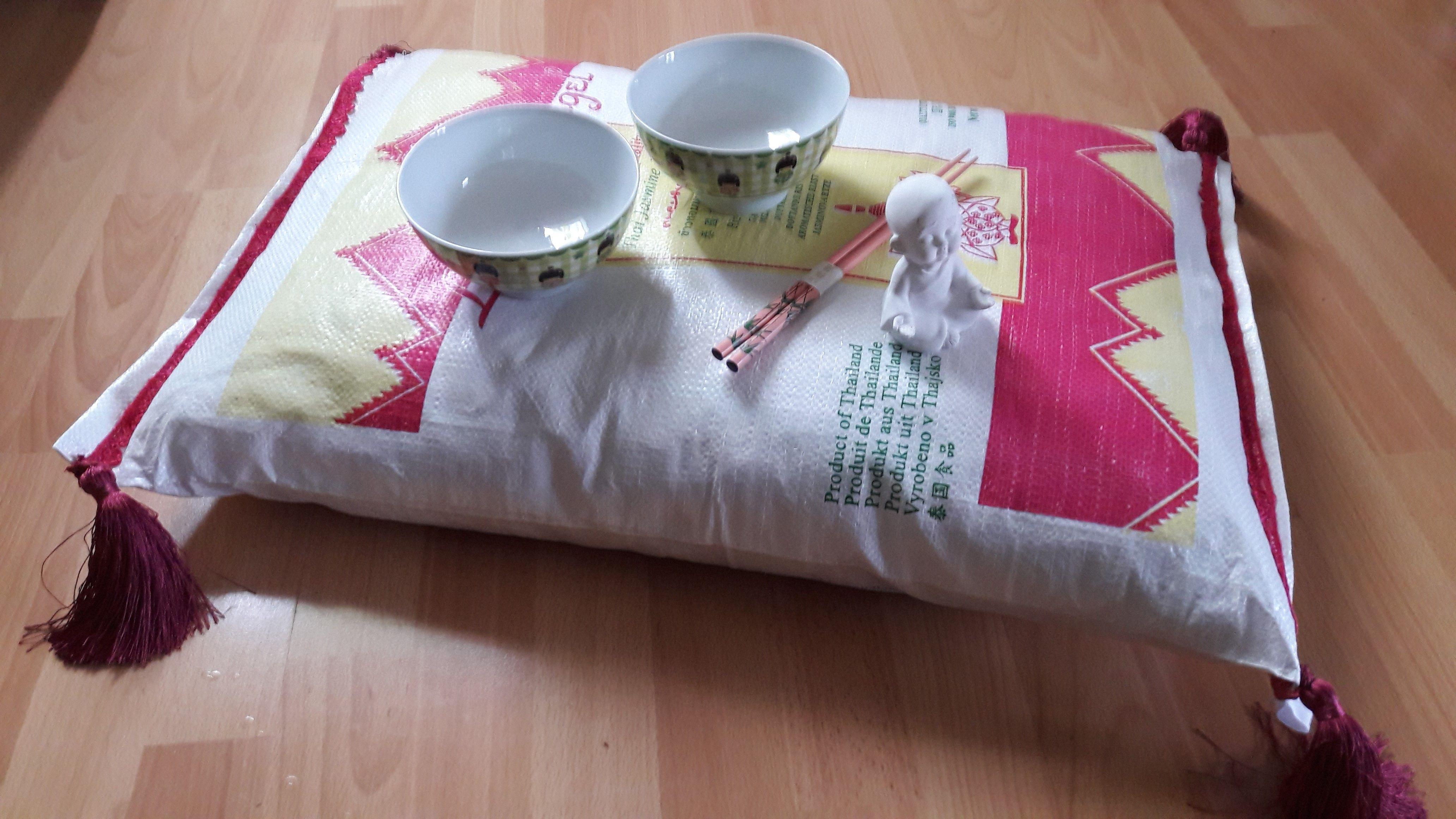 """Reissack wurde zum Sitzkissen oder zum kleinen Beistelltisch. Ausgestopft mit Fleecestücken und Stoffresten vom Nähen. An den Enden je eine Quaste. Super für die Terrasse oder das """"asiatische"""" Wohn oder Esszimmer."""