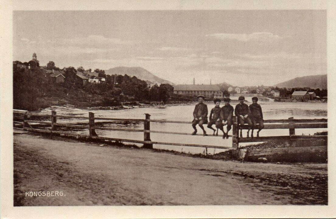 Kongsberg i Buskerud fylke . Gutter sitter på gjerde ved elven. Abels kunstforlag