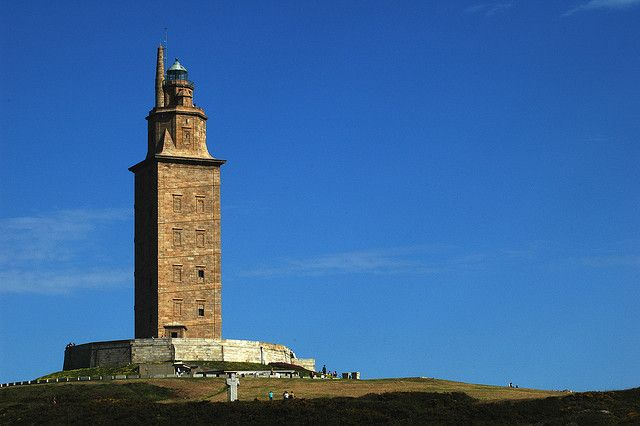 Tower of Hercules. Located in NW Spain  The Tower of Hercules is an ancient Roman lighthouse thought to be modeled after the Pharos Lighthouse of Alexandria. The tower has been in constant use since the 2nd century and considered to be the oldest existing lighthouse in the world. Originally it was constructed with an ascending ramp encircling its sides, for oxen to bring cartloads of wood to keep the light fueled at night. In 1788 the original 34 meters (112 feet)