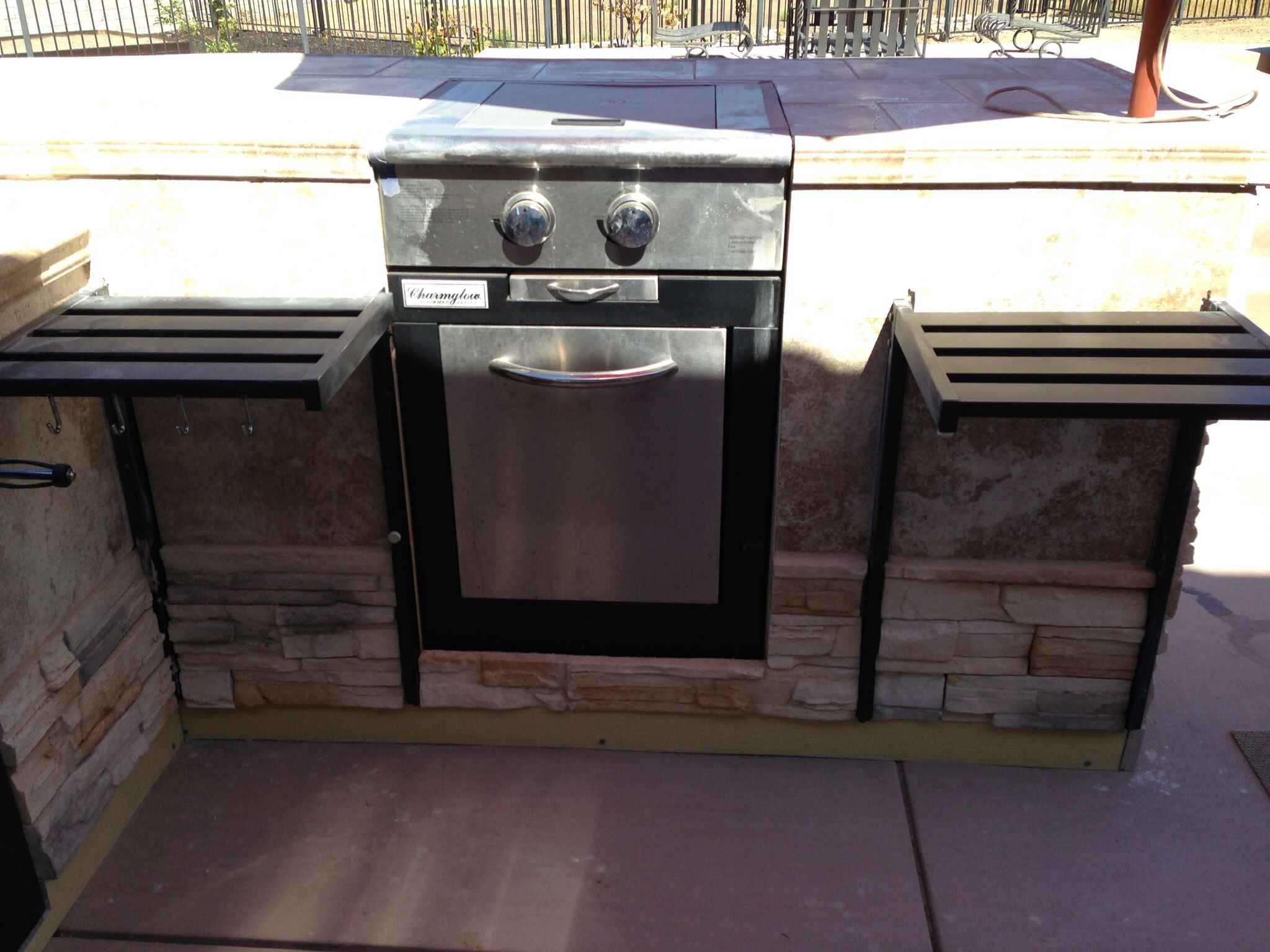 Set Into The Counter Top Is A Covered Propane Grill With A Refrigerator