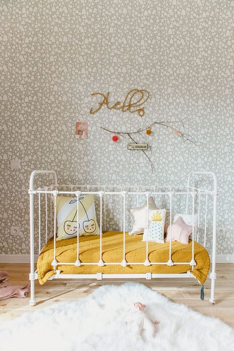 vintage inspired room with small floral wallpaper, white iron crib