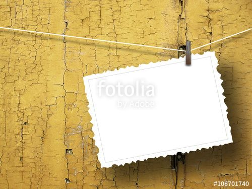 Close-up of one blank postcard frame hanged by peg against ochre weathered wooden background