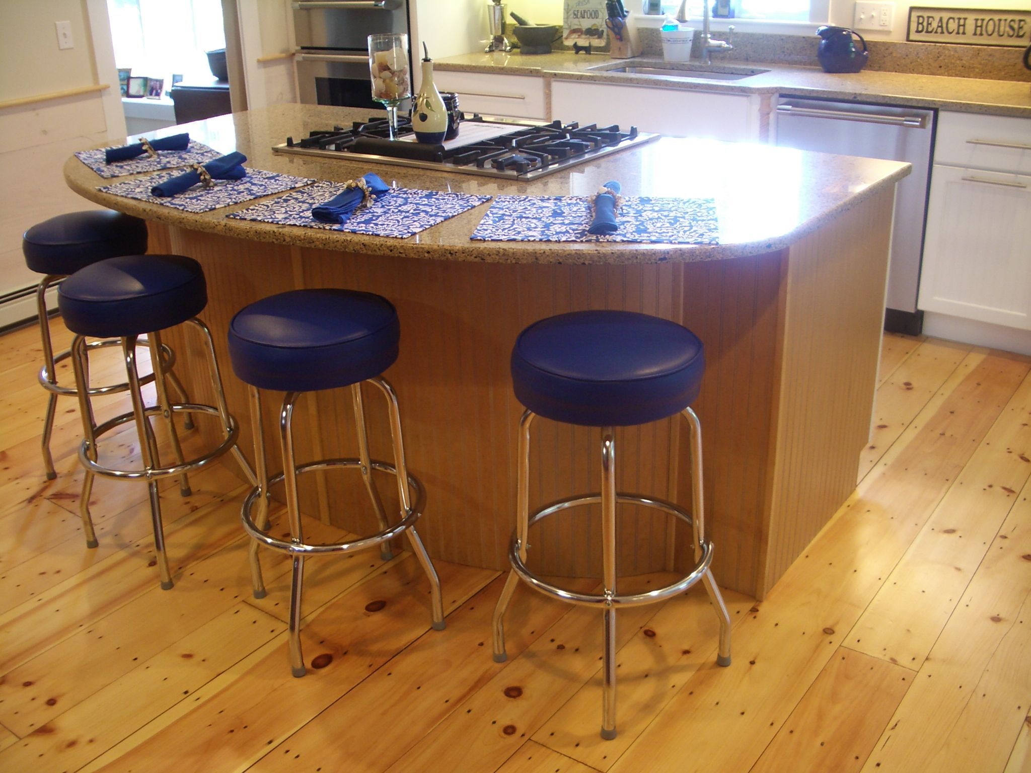Kitchen island wide pine floors blue stools countertop overhang