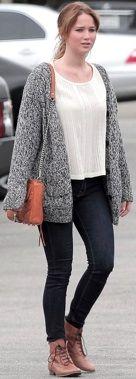 Jennifer Lawrence wearing dark skinny jeans, a loose white top, marled cardigan, and structured orange bag with flat lace-up boots