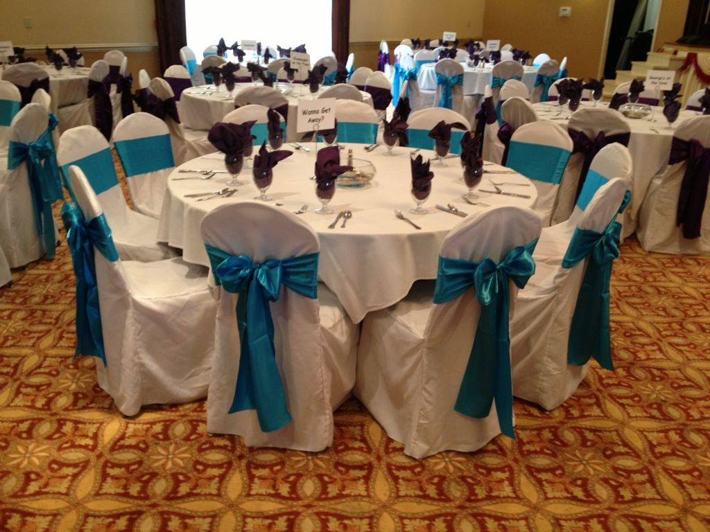 Purple And Turquoise Sashes On White Chair Covers For Engagement Party.