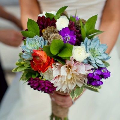 Unique Colorful Bridal Bouquet The bride selected a colorful mix of a lot of unique flowers such as succulents, dahlias, ranunculus, scabosia pods and islamic greens, combined with her bridesmaids using the same blooms but smaller.